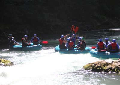 Several groups in mini rafts, lifting paddles in the air on the White Salmon middle gorge.