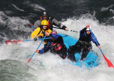Four people in a raft learning to navigate rapids.