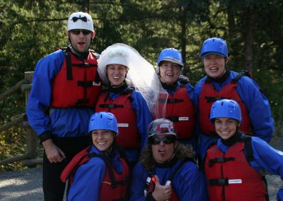 Wedding party posing for a group photo in their rafting gear. The groom is wearing a special white rafting helmet with a bow tie and the bride is wearing a white rafting helmet with a veil on it.
