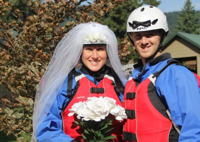 A bride and groom posing together in their rafting gear. The groom is wearing a special white rafting helmet with a bow tie and the bride is wearing a white rafting helmet with a veil on it.