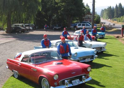 Group of people in their rafting gear posing in front of several vintage cars parked at Zoller's.