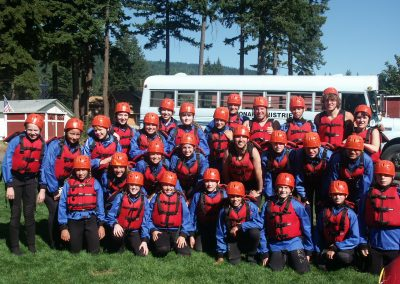 Twenty five young kids posing in their rafting gear.