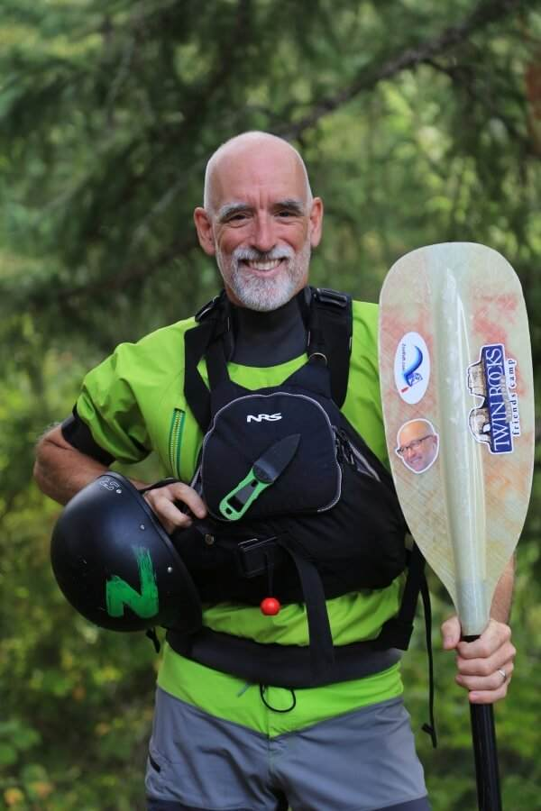 Older male guide and company owner, Mark, holding his raft paddle and smiling.